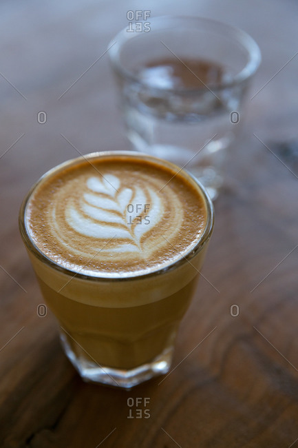 Cortado with rosetta leaf on wooden table