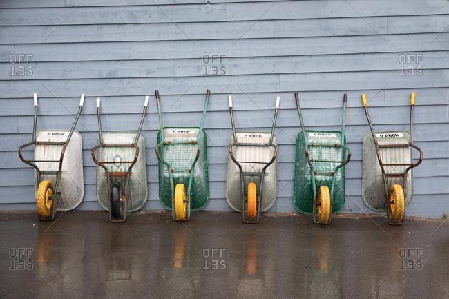 Victoria, British Columbia, Canada - April 30, 2020: Wheel barrows lined up on wall at a boat marina
