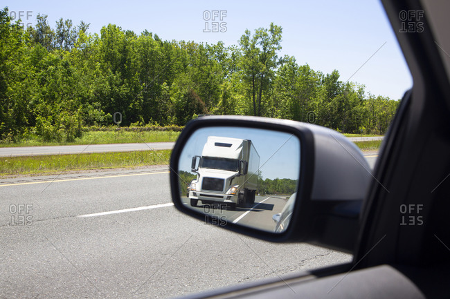 Semi trailer truck in rear view mirror driving on highway in northern New York State