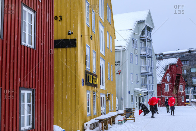March 6, 2020: Tourists, colorful historic wooden buildings, heavy snow in winter, Tromso, Troms og Finnmark, Arctic Circle, North Norway, Scandinavia, Europe