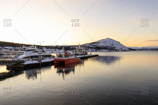 March 3, 2020: Port, ferry and boats, Altafjord, sea, mountains, snow, winter sunset, Alta, Troms og Finnmark, Arctic Circle, North Norway, Scandinavia, Europe