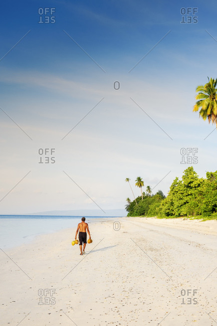 A local man carrying raw coconuts along a pristine beach, Manawoka Island, Maluku, Spice Islands, Indonesia, Southeast Asia, Asia