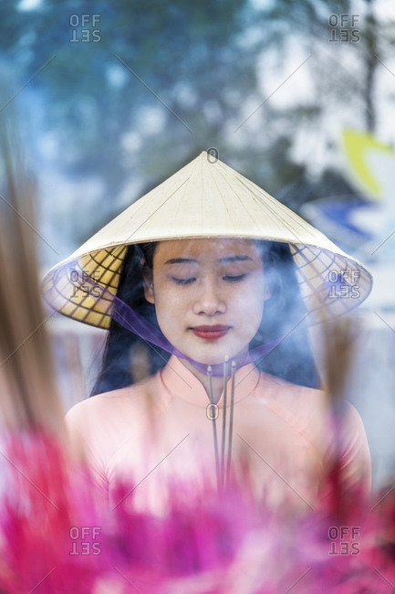 January 9, 2019: A young Vietnamese woman in a conical hat making incense offerings at a Buddhist temple, Hue, Vietnam, Indochina, Southeast Asia, Asia