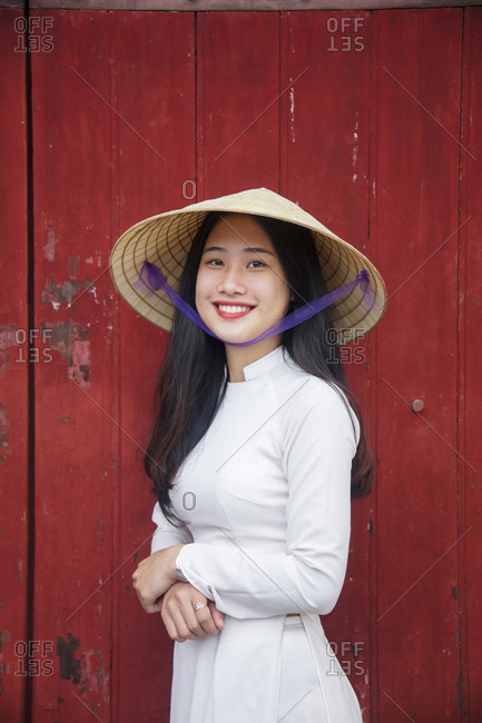 January 10, 2019: A young Vietnamese woman in traditional dress standing at the Western gateway to the Purple Forbidden City, Hue, Vietnam, Indochina, Southeast Asia, Asia