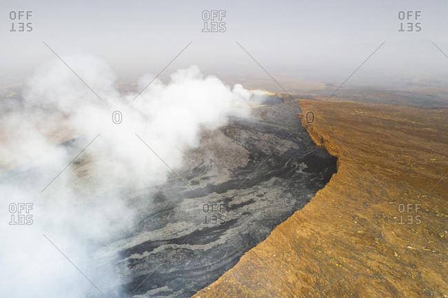 Arid soil on edge of the smoky Erta Ale volcano from above, Danakil Depression, Afar Region, Ethiopia, Africa