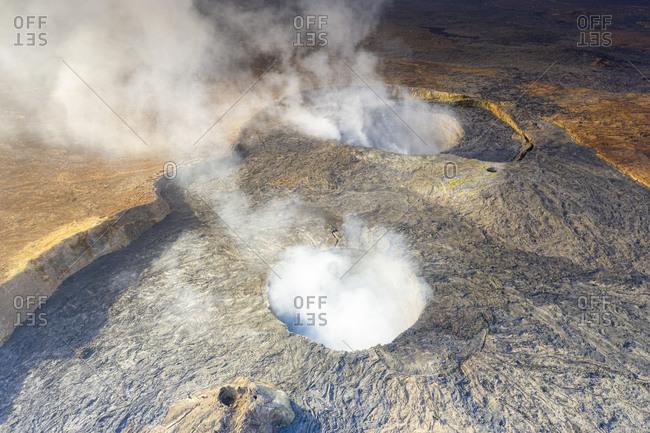Smoke over the two craters of Erta Ale volcano summit caldera, Danakil Depression, Afar Region, Ethiopia, Africa