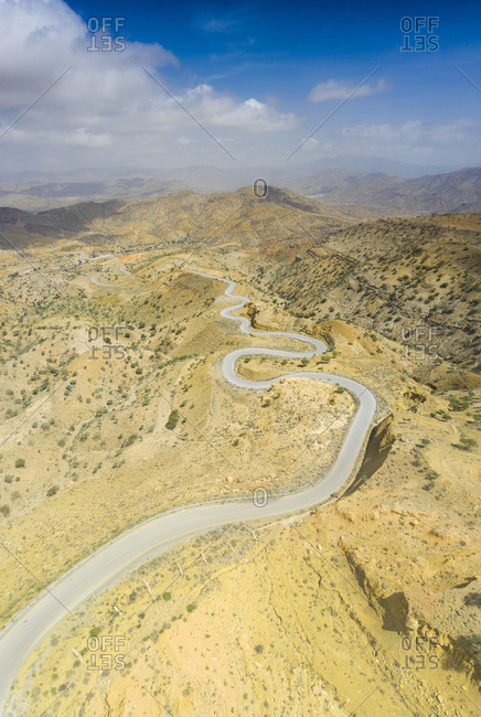 Panoramic view by drone of winding road towards Berhale crossing the dry landscape of Danakil desert, Afar Region, Ethiopia, Africa