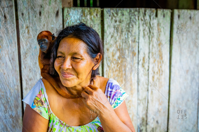 March 14, 2020: Woman and her rescued monkey at a local village on the Amazon River, Peru, South America