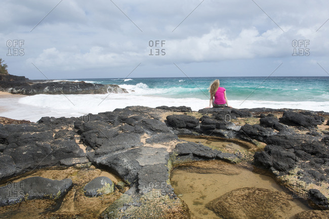 Sitting by a tidal pool on Secret Beach on the Hawaiian island of Kauai, Hawaii, United States of America, North America