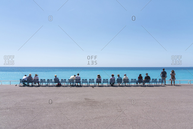 June 1, 2018: Line of people on chairs looking out to the sea, Nice, Alpes Maritimes, Cote d'Azur, French Riviera, Provence, France, Mediterranean, Europe