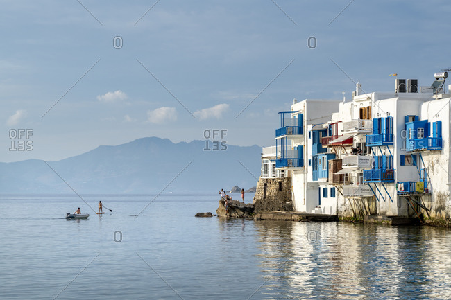 October 3, 2018: Paddle Boarder, inflatable boat and tourists on rock in Mykonos Town, Mykonos, Cyclades, Greek Islands, Greece, Europe