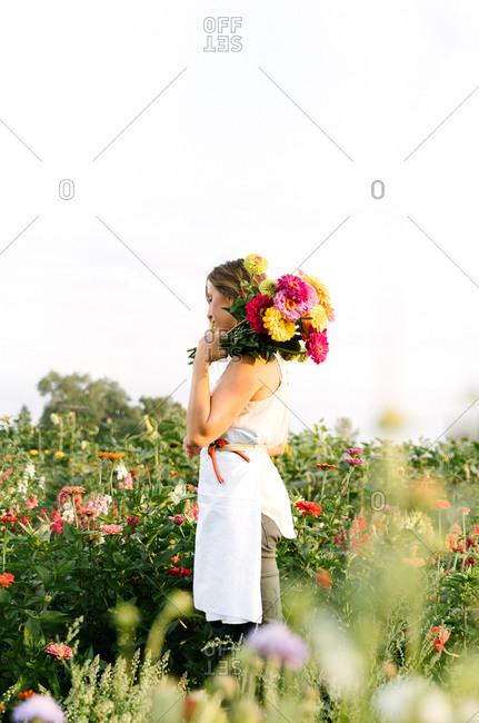 Caucasian woman walking with a bouquet Zinnias flowers in a field