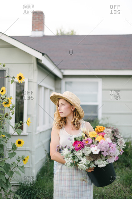 Caucasian woman holding a bucket of flowers in a field with a house behind