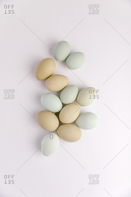A dozen of beautifully pastel toned eggs on a white background