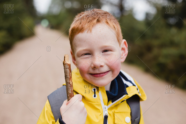 Portrait of redheaded little boy with wood stick