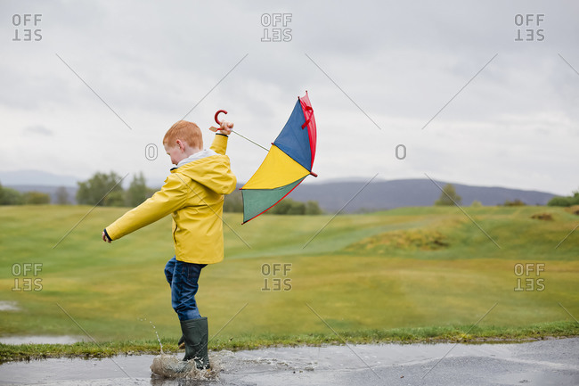 Redheaded little boy with umbrella playing in the rain
