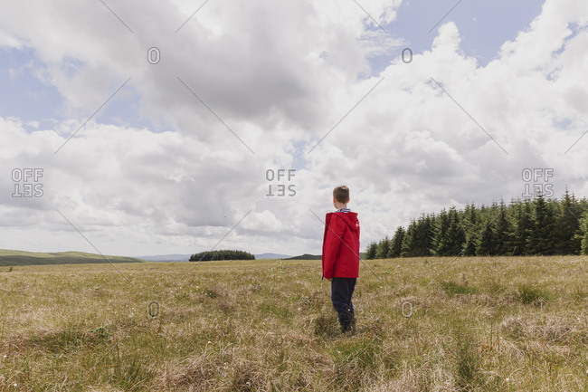 Back view of boy standing on a meadow watching clouds- Cairngorms- Scotland- UK