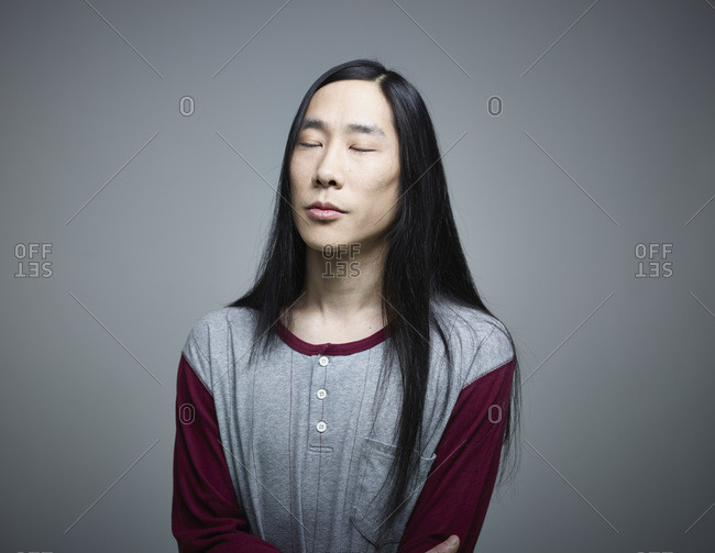 Mid adult man with eyes closed against grey background- close up