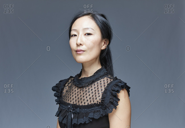 Portrait of self-confident woman in front of grey background