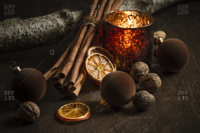Christmas decoration with tea light candle- christmas tree balls- cinnamon sticks- slices of dried oranges and walnuts on wooden table- studio shot