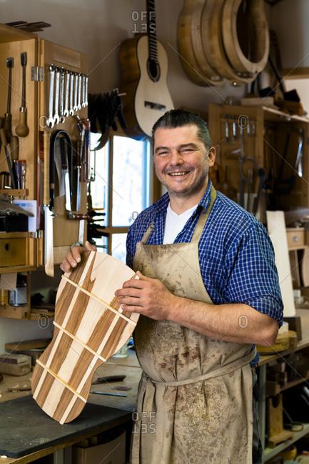 Smiling guitar maker in his workshop