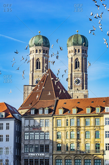 Germany- Munich- view to spires of Cathedral of Our Lady with houses and flight of birds in the foreground