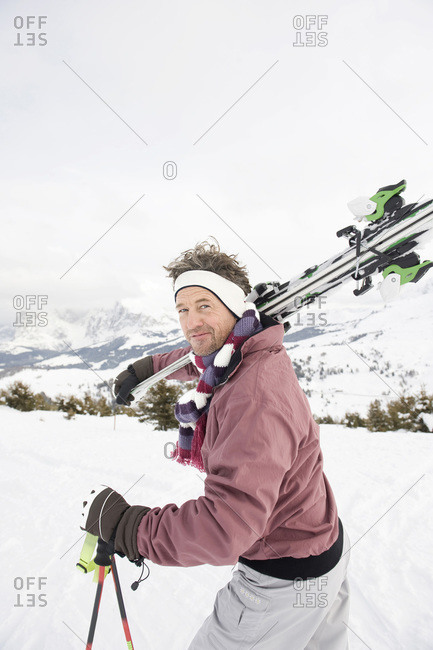 Italy- South Tyrol- Seiseralm- Man carrying skis- portrait