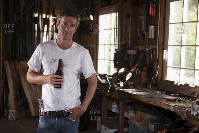 Germany- Hamburg- Man in home workshop holding beer bottle