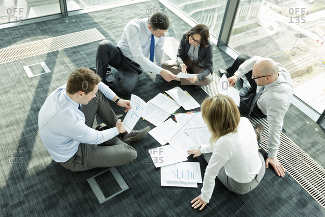 Businesspeople sitting on floor discussing papers