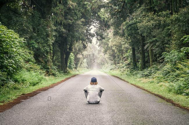 New Zealand- South Island- Jackson Bay- Haast Jackson Bay Road- young man sitting on road