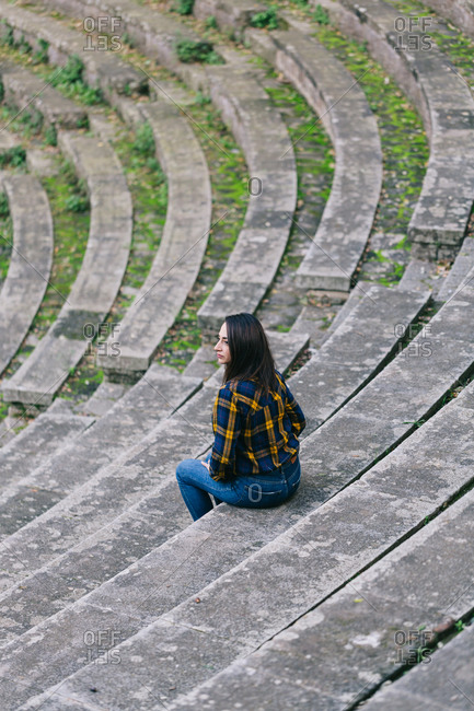 Woman sitting on the steps of an old open-air theatre
