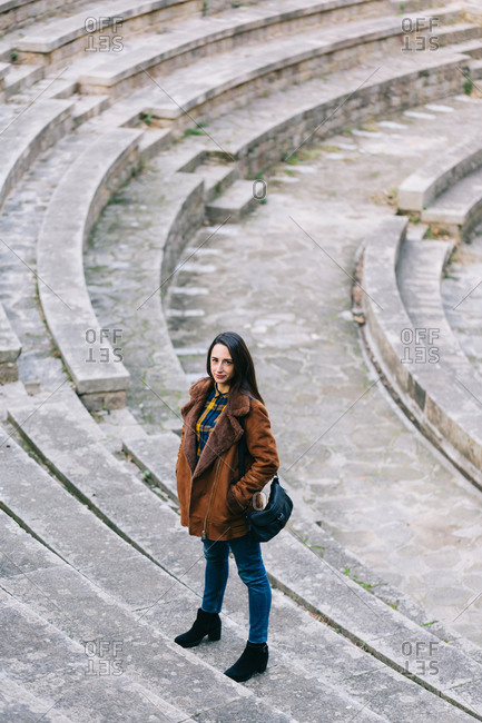 Portrait of a brunette woman in a brown jacket in an open-air theatre