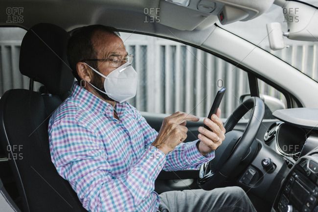 Senior man with face mask, using a phone inside a car