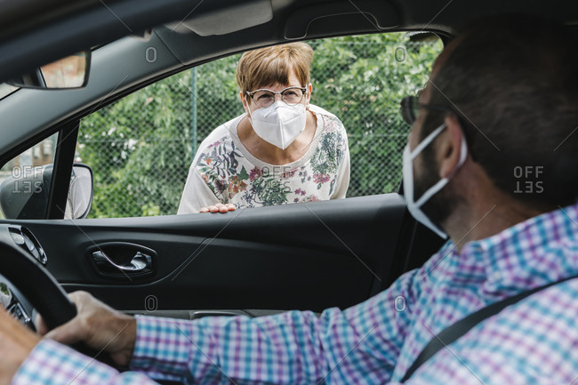 Masked man talking to a masked woman from his car while maintaining social distance