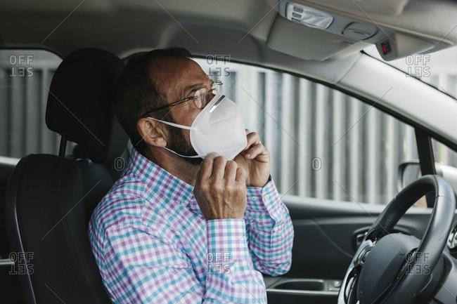 Senior man putting on face mask inside a car