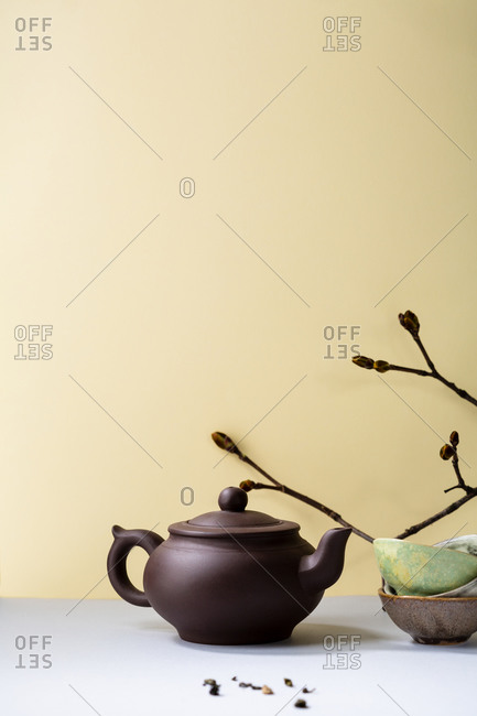 Brown small teapot against yellow wall