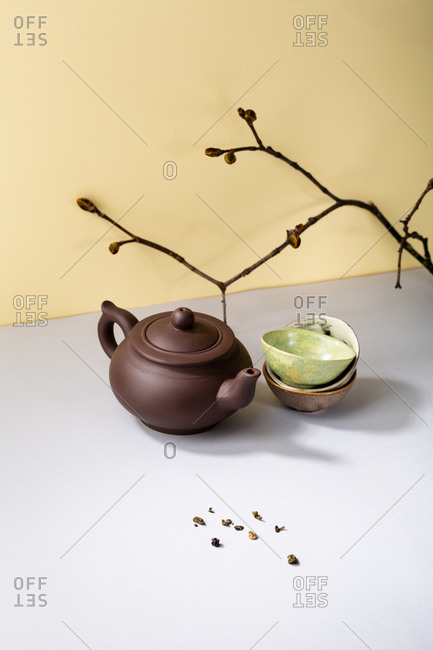 Ceramic teapot and cups against yellow wall