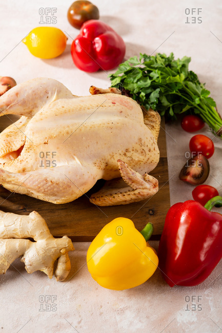 Whole uncooked chicken and vegetables