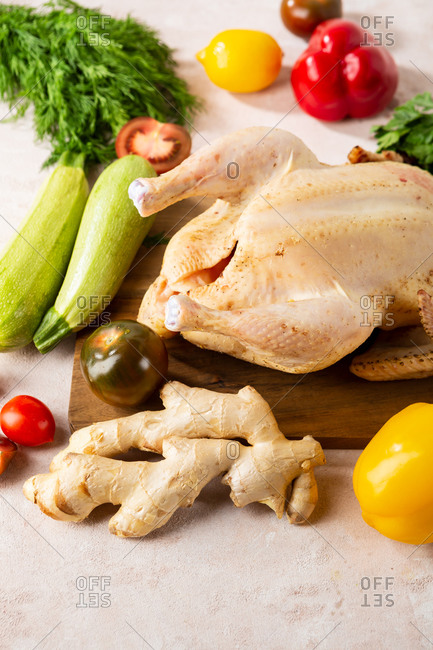 Whole uncooked chicken and vegetables on cutting board