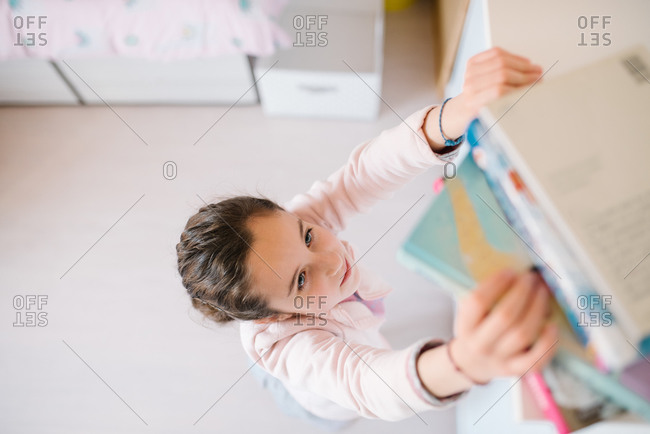 From above of curious schoolgirl in casual clothes reaching for book on high shelf to read at home