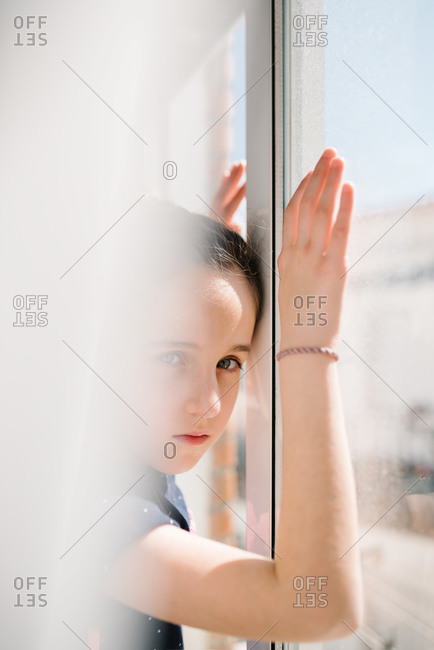 Side view of sad girl standing near window with hands on glass