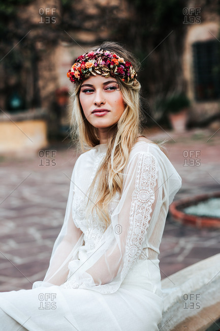 Pretty young woman in translucent white dress and floral wreath looking away while sitting on blurred background of yard on wedding day