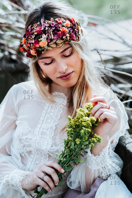 Beautiful young woman in white dress and floral wreath touching bouquet of small yellow flowers while resting in garden on wedding day