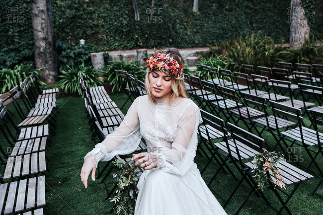 High angle of beautiful young female in elegant white dress and flower wreath closing eyes and sitting on empty chairs before wedding ceremony in garden
