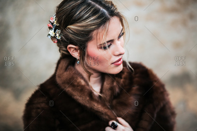 Elegant bride standing near shabby wall