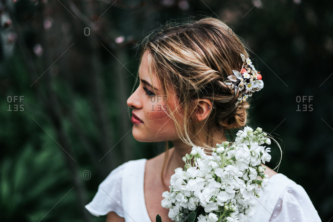 Pretty blond woman with bunch of white flowers looking away while standing on blurred background of garden during wedding on summer day