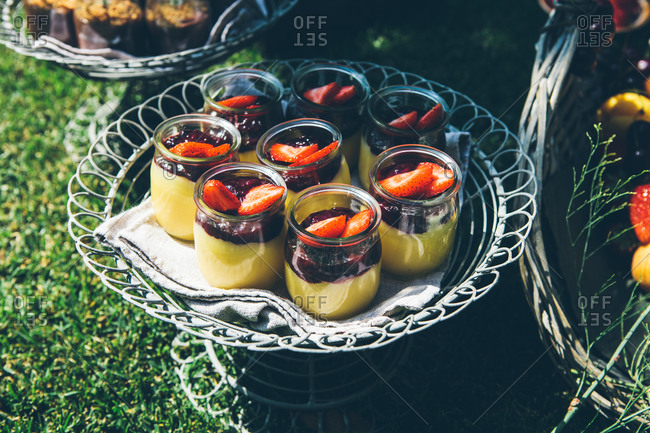Composition of fresh tasty desserts decorated with strawberry served in glass jars placed on round metal tray green lawn in garden