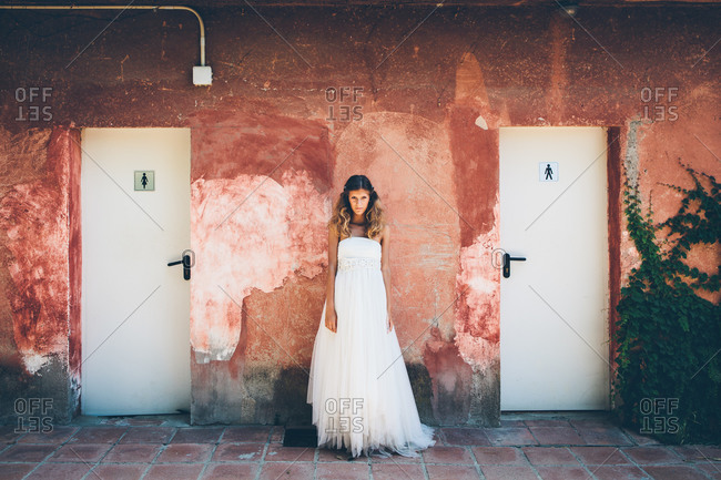 Charming young bride in elegant white wedding dress standing near red shabby wall near toilet doors and looking at camera