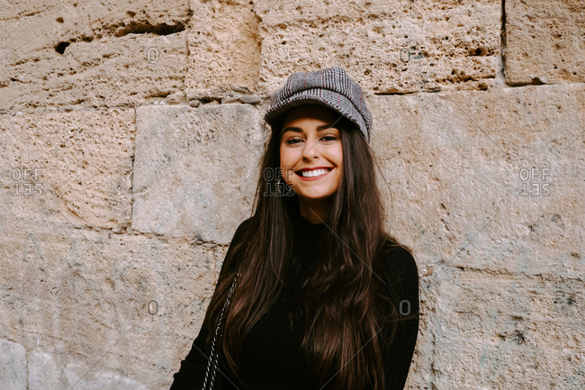 Happy young female in trendy hat smiling and looking at camera while standing near shabby wall of aged stone building