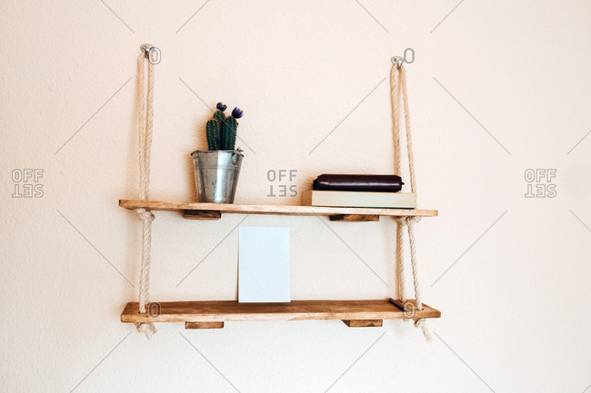 Rustic wooden shelf with houseplant and books in composition with blank white sheet of paper as mockup of photo hanging with cord on metal hooks on light beige wall of light apartment